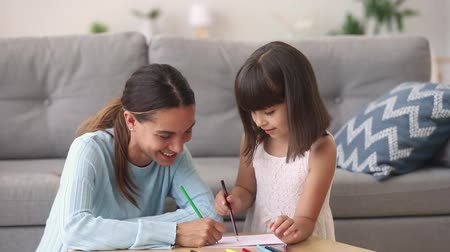 babysitter : Happy young mom baby sitter teaching coloring drawing with pencils talking to little girl at home, smiling mother nanny and child daughter play together, creative kid parent activity, babysitting