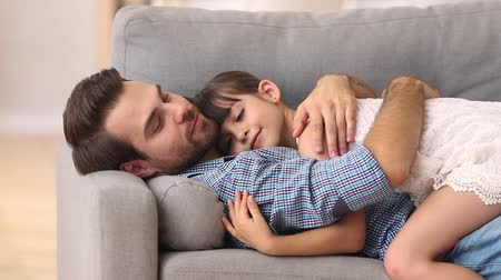 plezant : Happy father lying on sofa hugging cute little girl rest on comfortable couch, loving caring dad embrace kid daughter cuddling enjoy time together at home, daddy and child relax feel love connection