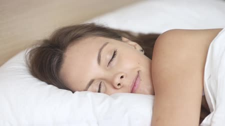 bastante : Calm young woman sleeping well in comfortable cozy fresh bed on soft pillow white linen orthopedic mattress, peaceful serene girl resting lying asleep enjoying healthy good sleep nap in the morning Stock Footage
