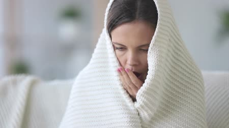 em casa : Covered with plaid young woman freezing feeling cold at home no central heating problem concept, ill sick girl having fever flu influenza temperature symptoms wrapped in blanket shivering indoors Stock Footage