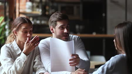 casal : Annoyed angry young couple customers clients holding papers arguing with manager having complaint on bad contract service demand claim insurance compensation meeting lawyer on legal fraud fight. Stock Footage