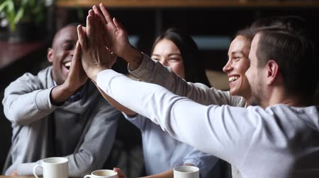 motivados : Diverse young happy friends join hands giving high five together celebrating multicultural friendship at reunion cafe meeting, multiracial mates students team bonding engaged in unity support concept