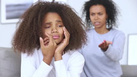 argumento : Sad teen african american girl upset by strict mum arguing scolding daughter, stressed stubborn teenager turned back ignoring angry black mother lecturing difficult kid, parent and children conflicts