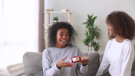 感謝の気持ち : Mothers day present concept, african american teen daughter make surprise congratulating happy excited black mommy closing mum eyes embracing mixed race mom giving gift box hugging on couch at home 動画素材