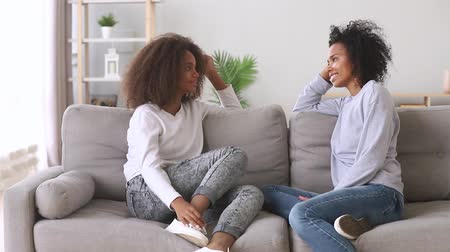 compreensão : Happy best friends african mother and teen daughter talking sitting on sofa at home, friendly black family loving mum with teenager girl chatting on couch share secrets having fun trust conversation