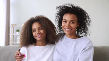 etnia africano : Happy african american family black mother and teen daughter make distance video call on looking at camera webcam having conversation talking laughing embrace communicate online recording vlog. Stock Footage