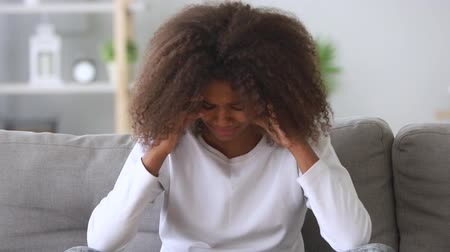 pranto : Upset depressed african american teen girl crying alone at home suffer from bullying being abuse victim, sad black school student teenager in tears feeling hurt offended ashamed having problem drama