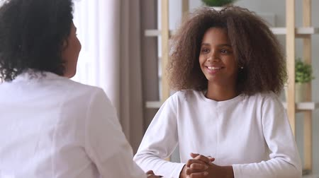 complaints : Smiling african american teenage girl listening to female doctor pediatrician school psychologist counselor talk to teen patient at checkup therapy consultation, pediatrist consulting black teenager