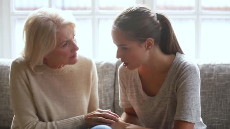 ciddi : Caring worried old senior mother holding hand consoling listening to young sad daughter talking sharing problems comforting upset young woman understanding helping giving advice love support empathy.