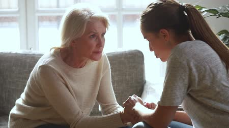 compreensão : Serious old mother and young daughter having trust conversation talking sharing problems giving advice care support, loving senior mom holding hands of adult woman comforting helping overcome problem Stock Footage