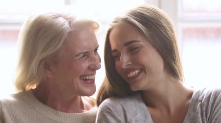 compreensão : Happy beautiful loving family old mature mother and adult daughter laughing bonding looking at camera, smiling senior mom with young woman having fun enjoy connection and warm relationships, portrait Stock Footage