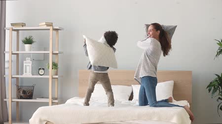 babysitter : Happy african american mixed race family mom baby sitter and little son having fun pillow fight on bed, young mother nanny laughing playing funny game with small child boy in bedroom on leisure time