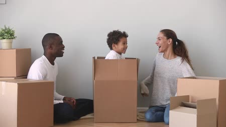 uitpakken : Happy mixed ethnicity family having fun unpacking boxes on moving day, cute kid child son jump out of box make surprise to african american dad and caucasian mom laughing enjoy relocation in new home Stockvideo