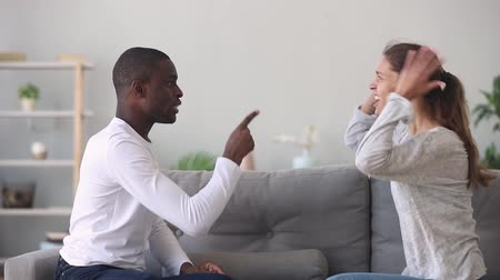 diffidenza : Angry emotional mad young mixed ethnicity couple argue at home, frustrated jealous african husband and stressed annoyed caucasian wife quarreling in family fight conflict, bad marriage relationships