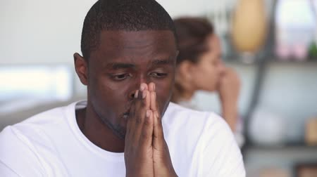 sulk : Sad thoughtful african american man feel upset after fight with girlfriend, upset depressed black husband tired of argument think of bad marriage, jealousy distrust in interracial couple relationship Stock Footage