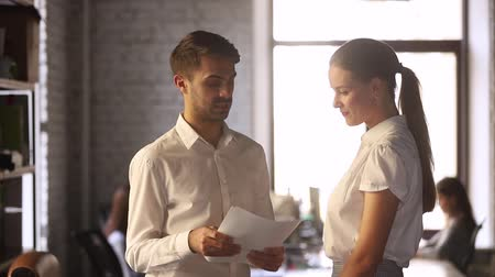 dankbaar : Male team leader boss discussing paperwork financial report with female manager thanking employee for good work result handshake expressing gratitude, making deal with client shake hands in office Stockvideo