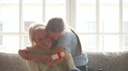 dankbaar : Little granddaughter making surprise hugging happy old grandmother presenting birthday gift box, preschool grandkid cute girl embracing excited senior grandma congratulating bonding sitting on sofa