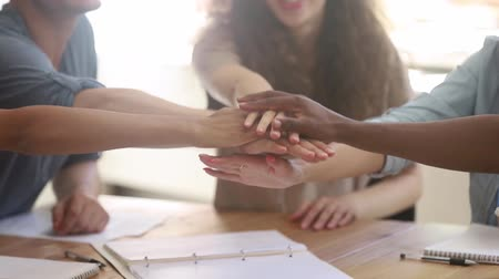 feliz : Multicultural happy team of business people students stack hands in pile together as teamwork and help, multi ethnic friendship concept, support in group work, unity trust cooperation, close up view Stock Footage