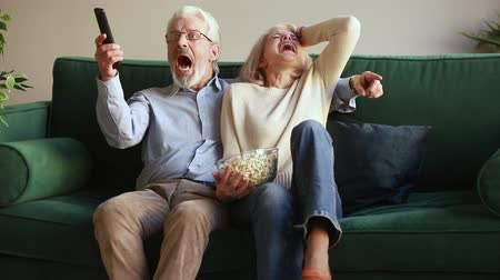 diváků : Happy senior aged couple football fans holding remote control watching sport tv game celebrate goal win victory together sit on sofa, excited euphoric old family supporting soccer team on television