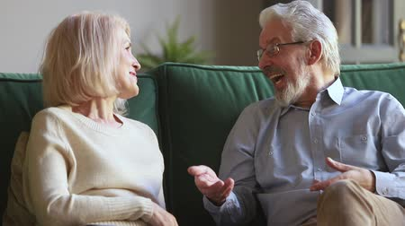 把握 : Senior spouses couple enjoy trust conversation sitting on sofa at home, understanding middle aged wife listening to honest elder husband joking sharing news flirting, old family soulmates casual talk 動画素材