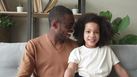 telefonia : Happy african father and little child girl vloggers recording vlog talking to camera at home, smiling black father with kid daughter looking at webcam make online video call , webcamera view