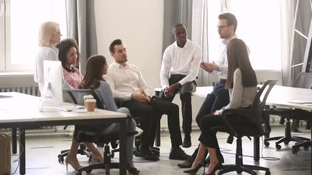 engaged : Male corporate team leader manager coach mentor teaching diverse workers group talking at company meeting, business teacher instructing training interns at workshop explaining new strategy in office
