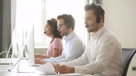 representante : Male call center agent wear wireless headset consulting online customer solving complaint use computer, business man operator talking working in service helpline support office with professional team