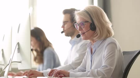 representante : Older mature business woman wear wireless headset working in customer service support office, senior aged call centre agent operator using computer consulting client with request or complaint