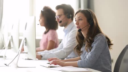 телемаркетинг : Young woman customer care support service agent call center operator in wireless headset talk consult online client using computer solving complaints on helpline or sell services in telesales office.