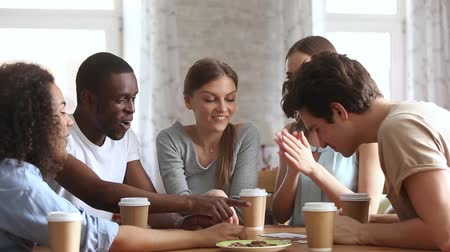 multinational : Cheerful millennial different ethnicity friends sit around the table chatting having fun assembling jigsaw puzzle put pieces together, enjoy free time and activities, unity synergy friendship concept Stock Footage