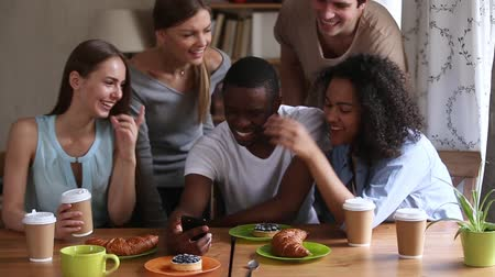 multinational : African ethnicity guy gathered with best friends in cafeteria coffeehouse holding smartphone show them new app laughing feels happy, modern wireless tech generation, multi-ethnic friendship concept Stock Footage