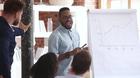 brifing : African friendly business coach teach company staff during corporate training, employee prepare presentation showing line graph sales stats company success on flip chart, mentoring education concept Stok Video