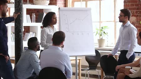 flipover : People gathered in office at corporate training, mixed race confident woman business trainer speaker explains to company staff diverse employees line graph data statistical chart shown on flip chart