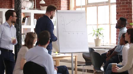 flipover : Multi racial company staff and business trainer gathered together in board room reporting sales statistics shown on flip chart line graphs, provide information giving knowledge at corporate training