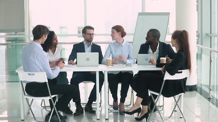 briefing : Diverse businesspeople gather together formal talk on meeting sit at table in modern office board room, business partners discuss possibilities of future collaboration, negotiations teamwork concept