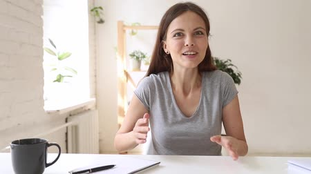 webinar : Overjoyed woman sitting indoors wave hand greeting associate telling unbelievable news to friend looking at web camera feels excitement, e-dating, making online call communication in internet concept