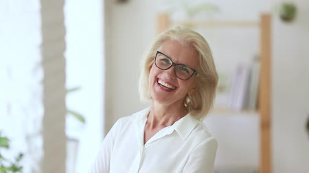 vision correction : Head shot of fifty years woman wearing glasses pose in office room looking at camera laughing feels happy, independent elderly company owner, coach or leader successful businesswoman portrait concept