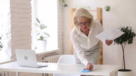 paçavra : Aged businesswoman holds rag wipes workplace desk prepares for workday negotiation meeting with client, to keep clean up table office room, healthy safety no dust, starts finish productive day concept Stok Video