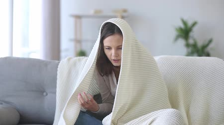 grzejnik : Young frozen woman sitting couch covered with white plaid warming up hands with breath feels unhealthy and discomfort spending time at home, cold season, need electric heater, domestic facilities debt