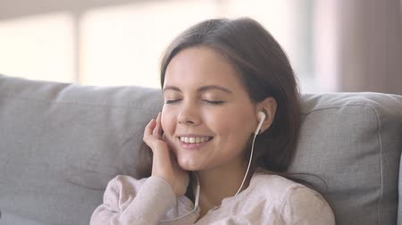 favori : Girl closed eyes resting leaned on couch listens song through earphones moves head in time favourite music open eyes look at camera having wide smile close up, lazy leisure activities at home concept Stok Video