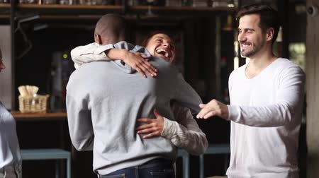arrive : Diverse girls guys stands meet greet african guy friends happy to see him at bar like-minded people welcoming give high five buddies embracing express respect, multiracial friendship reunion concept Stock Footage