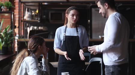 koffie verkeerd : Waitress girl justifies itself to customers clients for mixed up order, low-quality drink cold tea or coffee beverage, hysterical man talks with waiting staff complains about long poor service concept Stockvideo
