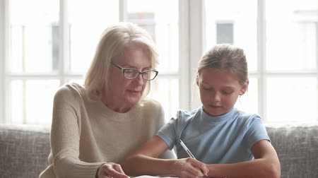 babysitter : Elderly private tutor or grandmother help to schoolgirl or granddaughter with homework explains material sit together on couch at home, apprentice girl writing down do task having lesson with teacher