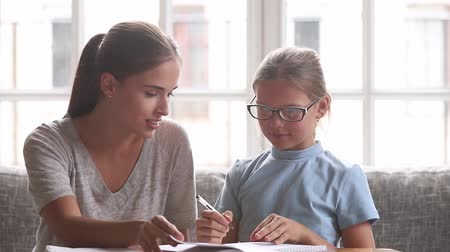 essay : Mother helping to schoolgirl daughter with homework, babysitter, older sister or private tutor teaching schoolchild girl in glasses doing task together, educational process support learning concept
