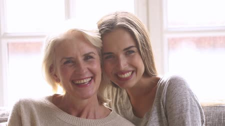 понимание : Head shot portrait of laughing grown up daughter hugging middle aged mother relative people sit on couch feels overjoyed posing looking at camera, good relations between different generations concept Стоковые видеозаписи
