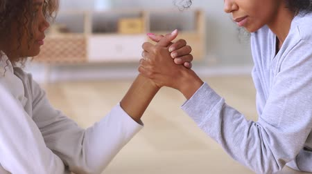 teen age : Mixed race women compete arm wrestle close up view, different ages generations sisters, mother and pre-teen grown up daughter having relations difficulties, generational gap, family conflicts concept Stock Footage
