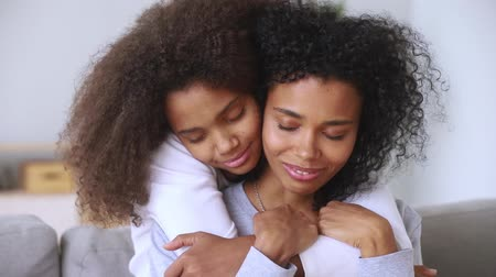 dankbaar : Close up view attractive afro biracial mother and grown-up pre-teen daughter or different ages sisters embracing on couch closed eyes enjoy moment of tenderness, love protection and gratitude concept