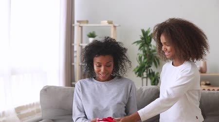 dankbaar : Afro teenage daughter cover mom eyes with hands prepared for her present, mixed race excited mum received from pre-teen kid gift box feels happy, parent hug child express gratitude, mother day concept