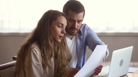 számla : Millennial couple sitting at table wife holding financial document young family analysing loan contract check lease agreement using computer online e-banking, planning budget expenses at home concept