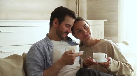 compreensão : Lovely newlyweds married couple in love sit on couch in living room talking feels happy, wife comfortably settled on the husband lap holding tea cups drink morning coffee enjoy cozy warm conversation